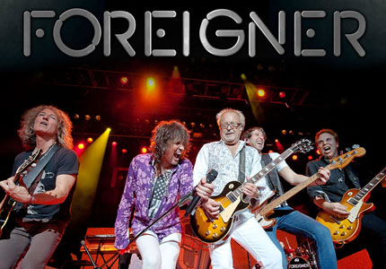five musicians from the band Foreigner playing on-stage